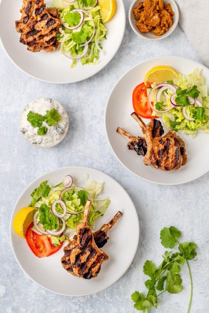 flatlay of 3 plates of Indian lamb chops