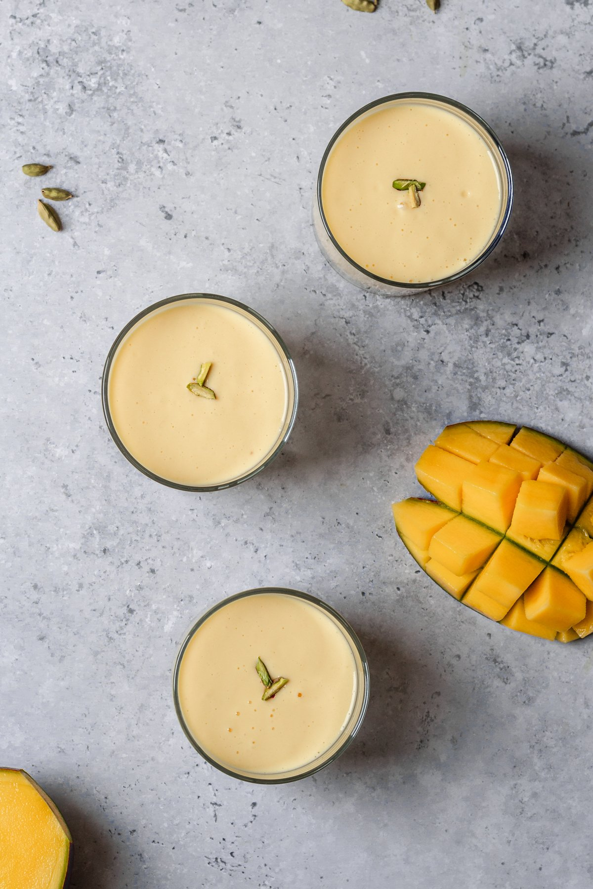 flatlay of 3 glasses of mango lassi